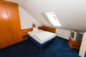 A bed or beds in a room at Hotel am Feuersee