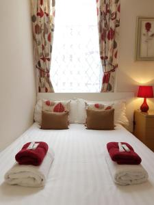 A bed or beds in a room at Bamford House Hotel