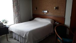 A bed or beds in a room at Mornington Hotel
