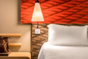 A bed or beds in a room at Hotel ibis Faro Algarve