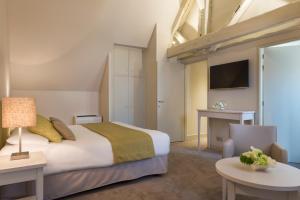 A bed or beds in a room at Hôtel Aux Vieux Remparts, The Originals Relais (Relais du Silence)