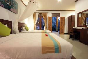 A bed or beds in a room at Budhi Ayu Villas and Cottages Ubud