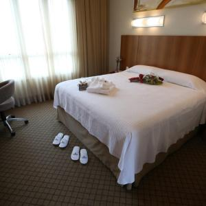 A bed or beds in a room at Bourbon Joinville Convention Hotel