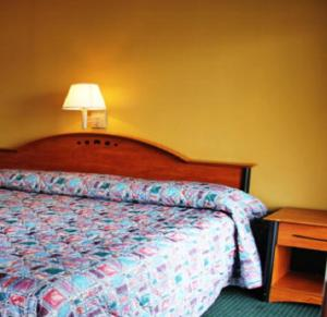 A bed or beds in a room at Speedway Inn