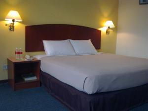 A bed or beds in a room at Hotel Caliber