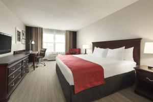 A bed or beds in a room at Country Inn & Suites by Radisson, Kansas City at Village West, KS