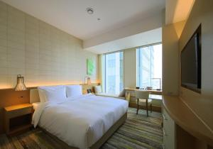 A bed or beds in a room at Nagoya JR Gate Tower Hotel