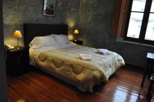 A bed or beds in a room at La Fresque Hotel