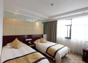 A bed or beds in a room at Huangshan Beihai Hotel