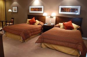 A bed or beds in a room at Howard Johnson Sierras Hotel y Casino Alta Gracia