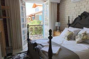 Cama ou camas em um quarto em Camboinhas Pousada Casa das Janelas Azuis