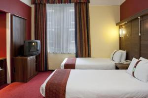 A bed or beds in a room at Holiday Inn London Oxford Circus, an IHG Hotel