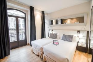 A bed or beds in a room at Petit Palace Chueca