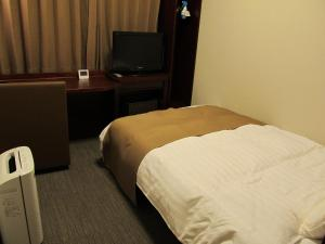 A bed or beds in a room at Dormy Inn Himeji Natural Hot Spring