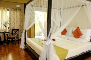 A bed or beds in a room at Sulu Sea Boutique Hotel