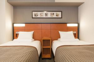 A bed or beds in a room at HOTEL MYSTAYS Sakaisuji Honmachi