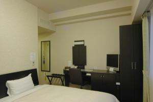 A bed or beds in a room at Hotel Route-Inn Kushiro Ekimae