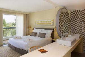 Uma cama ou camas num quarto em OZADI Tavira Hotel