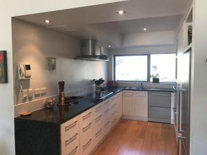 A kitchen or kitchenette at Oxley's Waterfront Luxury Apartment