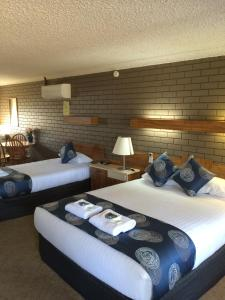 A bed or beds in a room at Tumut Valley Motel