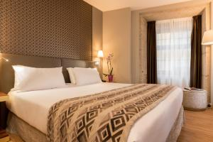 A bed or beds in a room at Exe Almada Porto