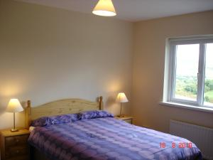 A bed or beds in a room at Bradleys Cottage Creeslough
