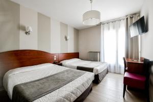 Un ou plusieurs lits dans un hébergement de l'établissement Hôtel Le Rupella