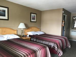A bed or beds in a room at Bulkley Valley Motel