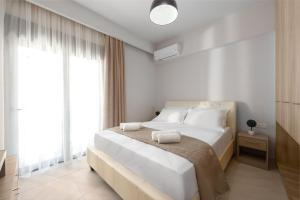 A bed or beds in a room at Lardos Luxury Apartments