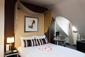 A bed or beds in a room at Hôtel Le M
