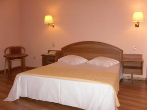 A bed or beds in a room at Grande Hotel Dom Dinis