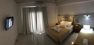 A bed or beds in a room at Atlantis Hotel
