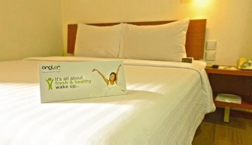 A bed or beds in a room at Whiz Hotel Malioboro Yogyakarta