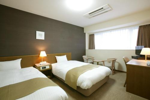 A bed or beds in a room at Hotel Montagne Matsumoto