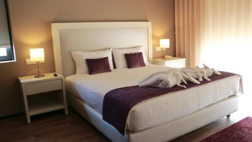 A bed or beds in a room at Monte Lírio Hotel & Wellness Centre