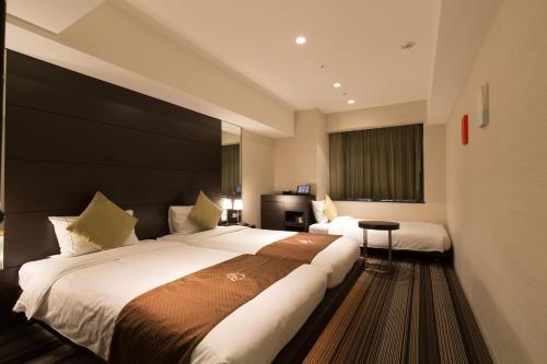 A bed or beds in a room at Hotel Brighton City Osaka Kitahama