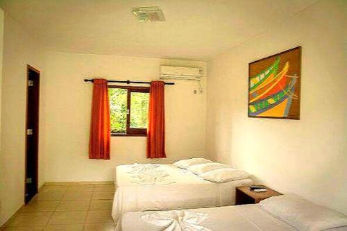 A bed or beds in a room at Pousada Sol da Trindade