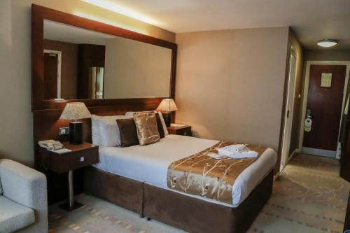 A bed or beds in a room at Alona Hotel