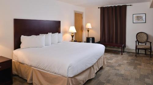 A bed or beds in a room at Canada's Best Value Inn – Downtown Hotel Dawson City