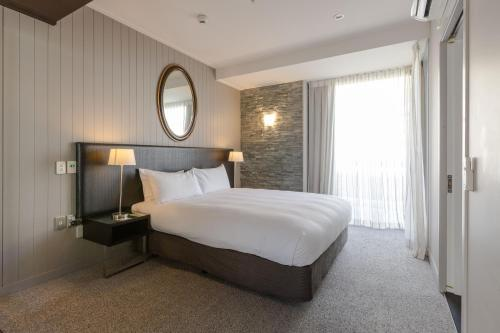 A bed or beds in a room at DoubleTree by Hilton Queenstown
