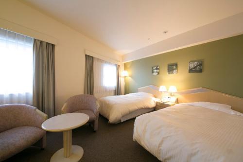 A bed or beds in a room at Shin Osaka Washington Hotel Plaza
