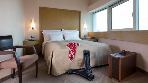 A bed or beds in a room at Enea Hotel Aprilia