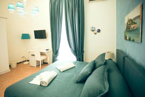 A bed or beds in a room at NapoliMia Hotel