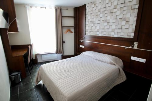 A bed or beds in a room at Hotel des Pyrénées