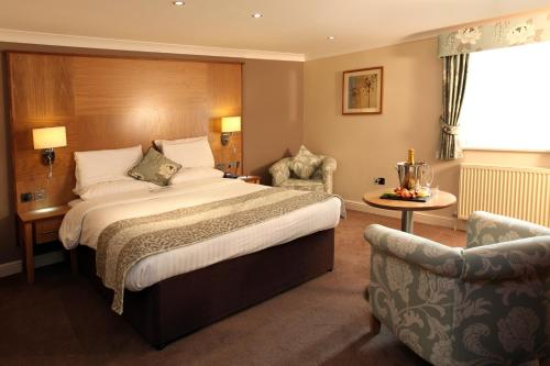 A bed or beds in a room at Best Western Premier EMA Yew Lodge Hotel