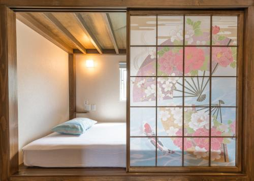 A bed or beds in a room at Maisan-chi Guesthouse & Cafe