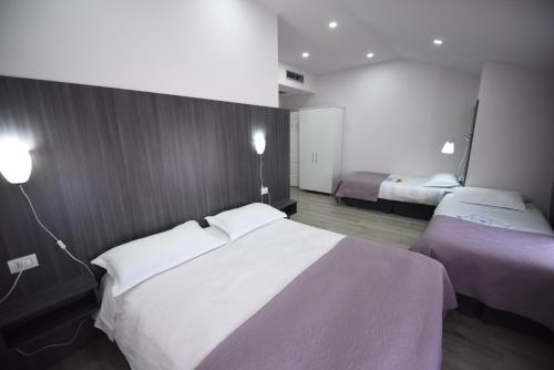 A bed or beds in a room at Rose Garden Hotel