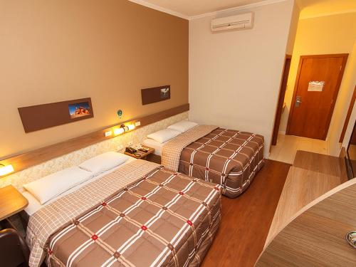 A bed or beds in a room at Hotel 10 Uniao da Vitoria