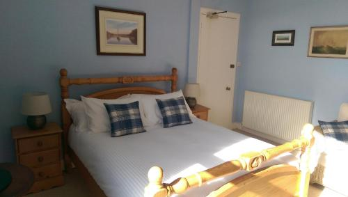 A bed or beds in a room at Lochinver Guesthouse