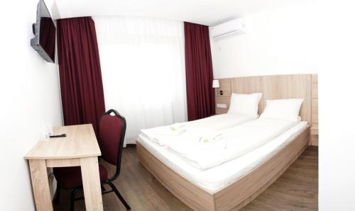 A bed or beds in a room at Pensiunea Otopeni